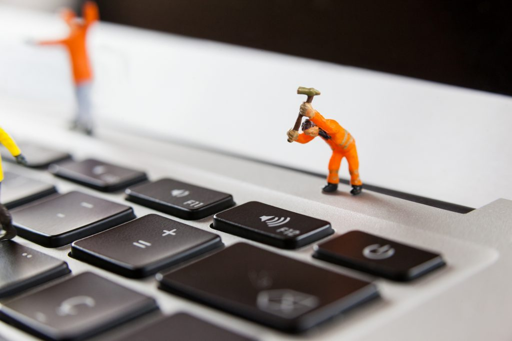 Miniature workmen repairing a laptop keyboard
